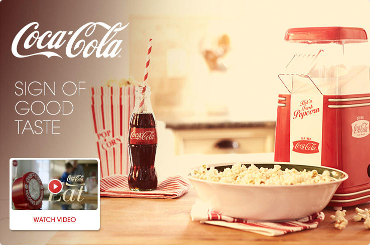 coca-cola sign of good taste. Coca-cola eats video. Watch video. a coke sits next to a bowl of popcorn.