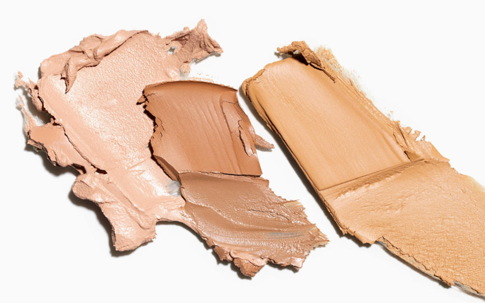 Samples of different shades of foundation smeared on a light surface