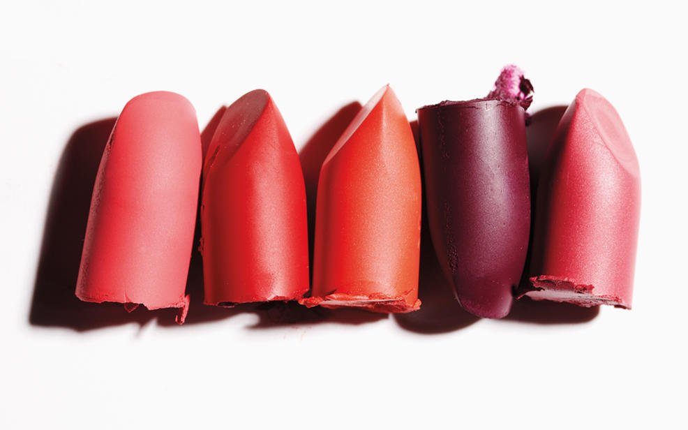 Several tops of lipsticks arranged in a line on a light surface