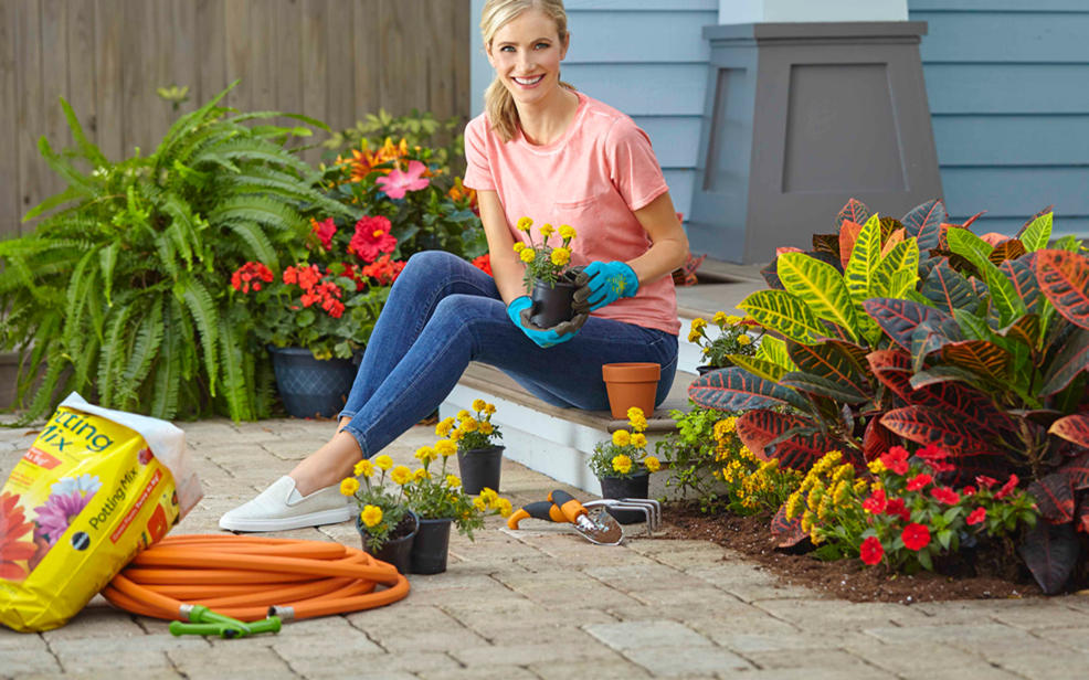 A woman sits in her garden holding a pot of flowers.