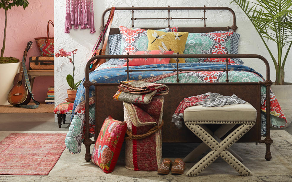 A bed with multi-colored sheets, piillows and exotic decorations.
