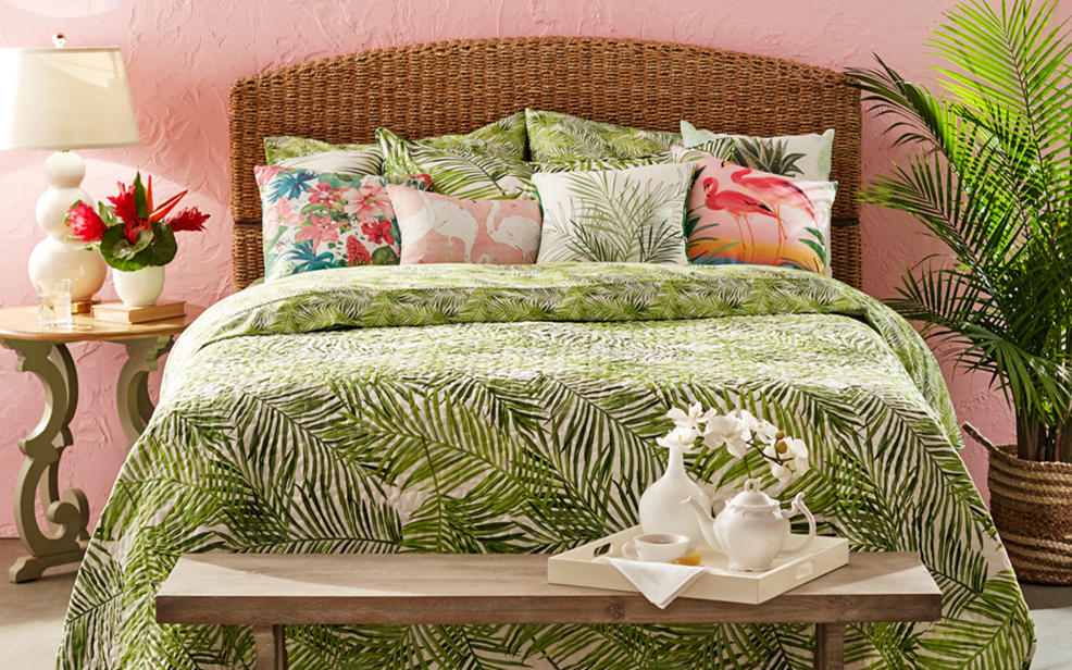 A bed with green sheets and piillows with a palm frond print. A serving tray at the base.