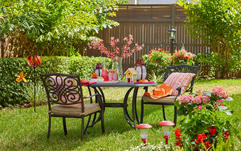 patio chairs next to a table in a green flowering yard