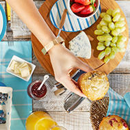a woman serves a fresh muffin over a plate for fresh fruit and cheese.