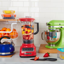 Colorful kitchen items. A blue teapot, a red blender, a green mixer.